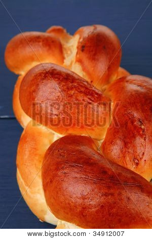 baked product : golden challah on blue wooden table poster