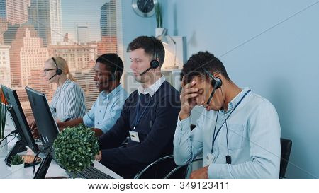 Bored And Dissatisfied Black Call Center Agent Talking To The Client On Phone. He Is Behaving Nervou
