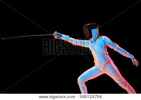 Attacking. Teen Girl In Fencing Costume With Sword In Hand Isolated On Black Background, Neon Light.