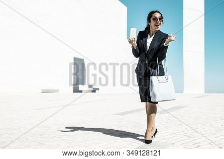 Excited Joyful Office Lady With Handbag Showing Phone. Young Woman In Formal Suit And Sunglasses Wal