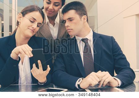 Smiling Business Woman Showing Smartphone Screen To Colleagues. Business Man And Women Reading News,
