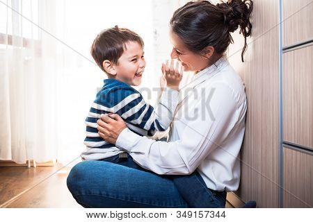 Beautiful Young Mom And Her Son, Sitting On The Floor Being Affectionate With Each Other. Hugging An
