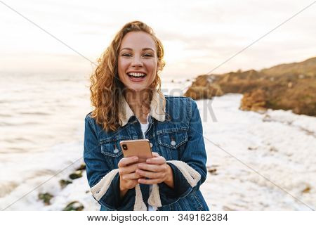 Image of young beautiful woman with blond curly hair using smartphone while walking by seaside