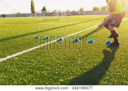 Soccer Football Training Run. Young Player Running Fast Between Training Cones Markers On Summer Day