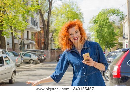 Taxi From App. Pretty Happy Woman Holding Mobile Phone, Hitch Hiking In The City Street On A Sunny D