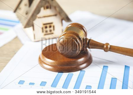 Judge With House Model On Graph On Desk
