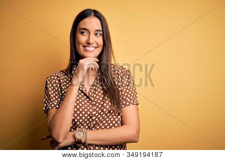 Young beautiful brunette woman wearing casual shirt over isolated yellow background with hand on chin thinking about question, pensive expression. Smiling with thoughtful face. Doubt concept.