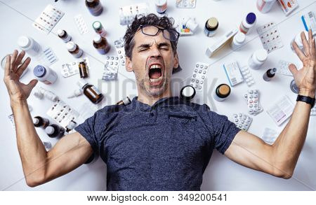 Crazy man isolated over pills background
