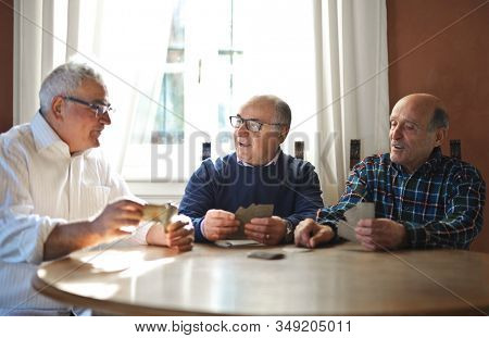 Senior men playing with cards together.