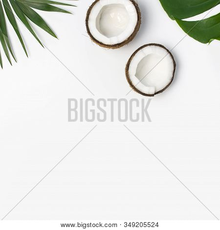 Tropical Leaves And Fresh Coconut On Light Gray Background Top View Copy Space. Summer Flat Lay Back