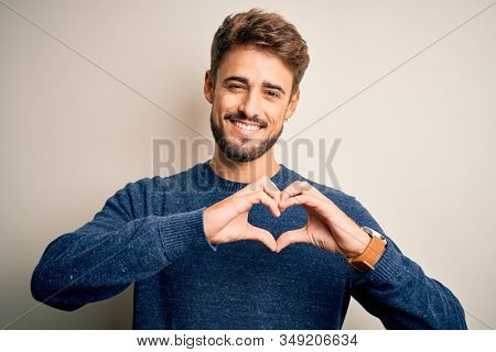 Young handsome man with beard wearing casual sweater standing over white background smiling in love showing heart symbol and shape with hands. Romantic concept.