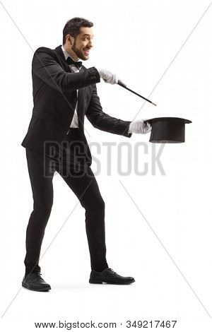 Full length shot of a wizard making a magic trick with a wand and a tophat isolated on white background