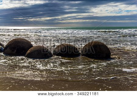 Ocean tide begins. Group of large round boulders on the coast of the South Island of New Zealand. Moeraki boulders. Sunset. The concept of active, ecological, exotic and phototourism