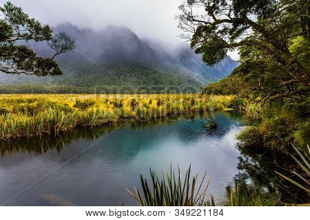 New Zealand. The majestic nature of the South Island. Misty morning on the way to Milford Sound. Clouds and fog cover the mountains. Mirror Lake. The concept of exotic, active and phototourism