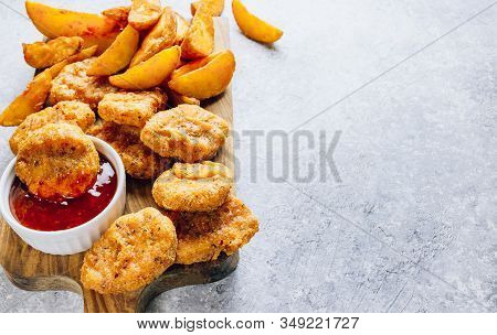 Serving On A Wooden Board Crumbed Fried Nuggets With Fried Potato And A Small Bowl Of Sauce Or Dip O
