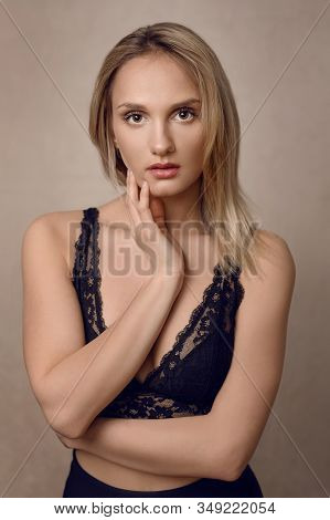 Attractive Young Blond Woman In Sexy Black Lacy Lingerie Staring Intently At The Camera With Her Han