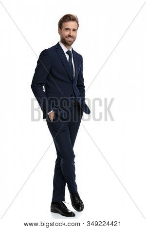 happy businessman in navy blue suit holding hands in pockets and smiling, standing isolated on white background, full body