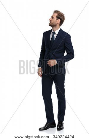 confused young man in navy blue suit looking up and standing isolated on white background, full body