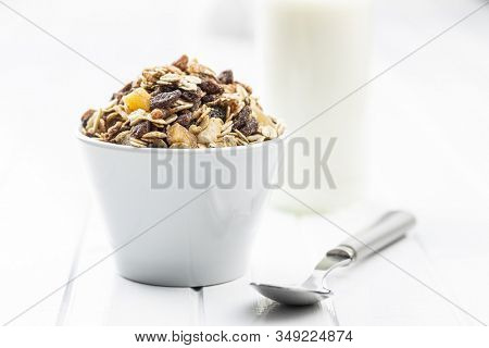 Healthy cereal breakfast. Mixed muesli in bowl on white table.