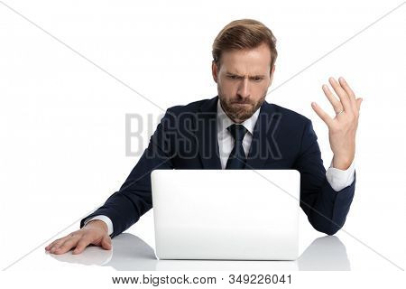 mad businessman in navy blue suit reading emails and sitting isolated on white background