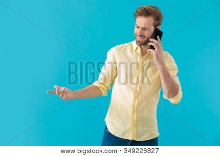 Bothered casual man disagreeing on his phone and gesturing while looking away and standing on blue studio background