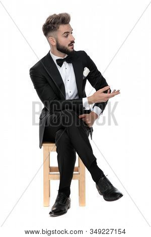 young businessman wearing black tuxedo sitting on a wooden chair with legs crossed and talking with someone to aside intrigued on white studio background