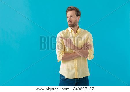 Bothered casual man pointing to the side and indicating while holding his arms crossed, standing on blue studio background