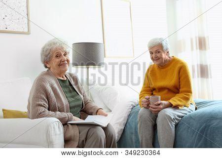 Elderly Women Spending Time Together In Bedroom. Senior People Care