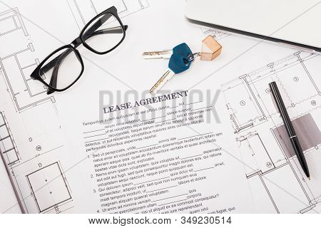 Top View Of Document With Lease Agreement Lettering Near Glasses, Blueprints And Keys On Desk