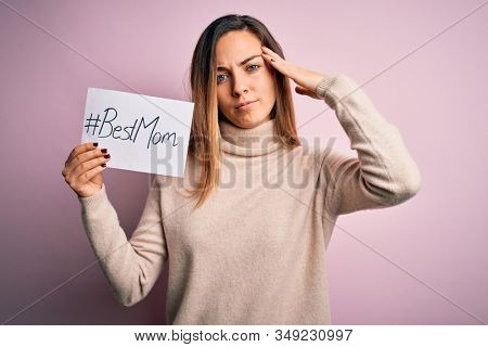 Young beautiful woman holding paper with best mom message celebrating mothers day stressed with hand on head, shocked with shame and surprise face, angry and frustrated. Fear and upset for mistake.