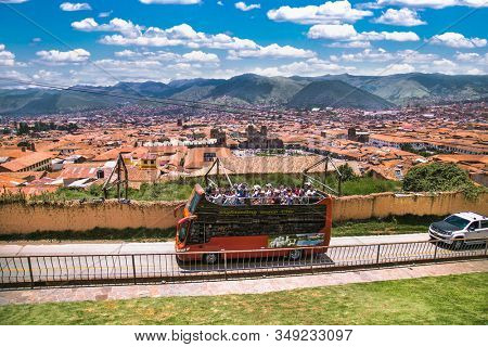 Cusco , Peru- Jan 9, 2019: Double-decker hop-on hop-off bus with tourists seen in front of  San Cristobal  church and panoramic view on Cusco city, Peru.