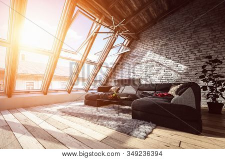 Attic living room interior with cozy corner couch, furry carpet and warm sunlight coming from wide panoramic windows. 3d Rendering