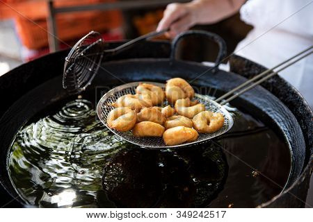 Cook Holds A Serving Of Freshly Baked Donuts On Sieve, Just Lifted From The Oil. Delicious Fast Food