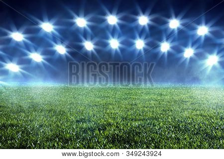 Double Arc Of Spotlights Shining On An Empty Sports Field With Green Grass And Mist At A Stadium Con