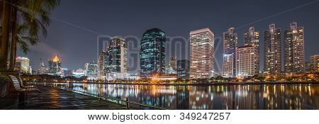 A Bench Near The Lake In Benjakiti Park With Skyscrapers At Night In Bangkok, Thailand