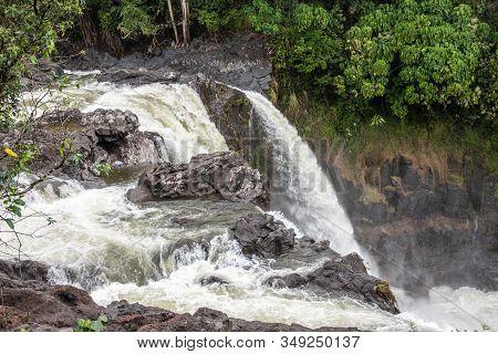 Hilo, Hawaii, Usa. - January 14, 2020: Closeup Of White Water Falling Over Lava Rocks On Edge Of Rai