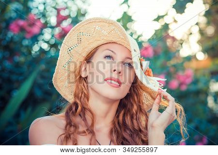 Daydreaming. Lifestyle Woman Relaxing Enjoying Weather Thinking Looking Up Pensive Holding Her Hat O