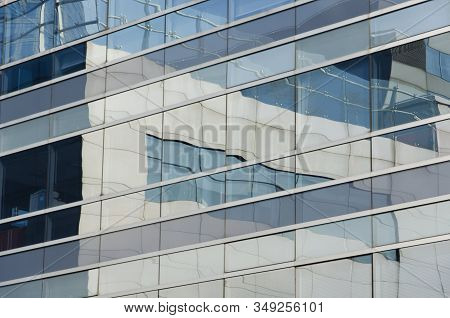 Reflective Building In Which The Surrounding Ones Are Reflected. Image Of Parallel And Perpendicular