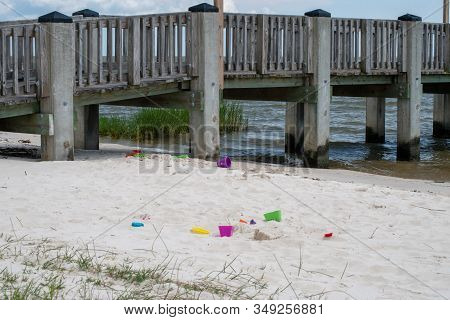 An Ocean Pier Against A Blue Sky With Beach Toys Left Near The Waters. Gives A Feeling Of Lonliness