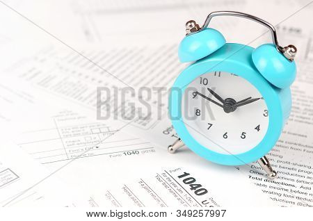 1040 Individual Income Tax Return Form And Blue Alarm Clock