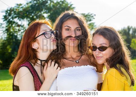 Girl With Two Friends Funny Portrait In Park.