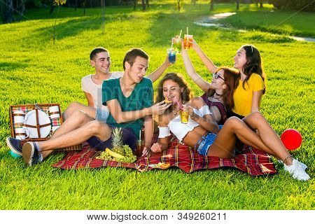 Cheerful Young People Drinking Cocktails On Picnic.