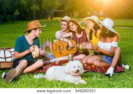 Group Of Young Friends Having Fun On Picnic Party, Sitting Together On Green Lawn In The Park, Girl