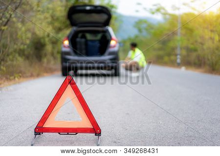 Breakdown Triangle Sign On Road With Worried Asian Man Repairing And Change Tire While Waiting Insur