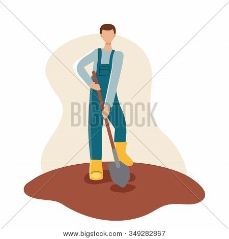 A Male Gardener In A Yellow Boots And Blue Robe Holds A Shovel And Digs Up The Ground. Spring Planti
