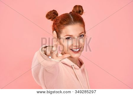 Portrait Of A Wavy Curly Gorgeous Young Caucasian Ginger Woman Smiling Toothily Showing You One Fing