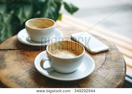 Two Cups Of Coffee And A Cellphone On A Wooden Table In A Cozy Cafe. Concept Of Meeting People Or Mo