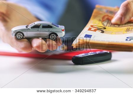 Money Loan Car Pledge Concept. Scale Model And Money In A Hand