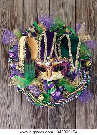 Mardi Gras Wreath On Old Wooden Door With Mardi Gras Mask.