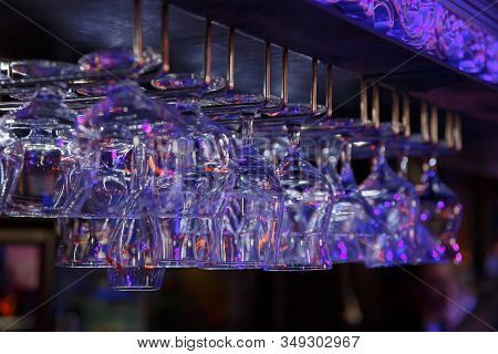 Empty Wine Glasses Hanging Over A Bar Rack In A Nightclub. Dark Background